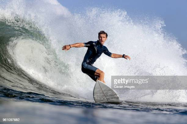 low angle view of man surfing on sea - surf fotografías e imágenes de stock