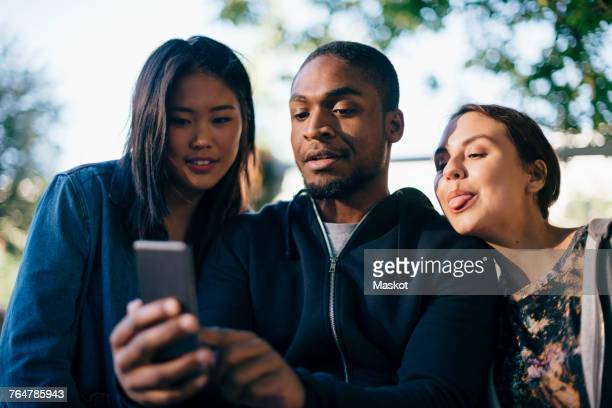 Low angle view of man taking selfie with female friends