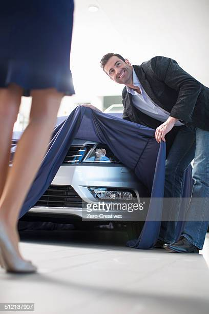 Low angle view of man uncovering new car for girlfriend in car dealership