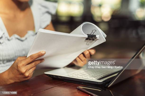 low angle view of man using mobile phone on table - law stock pictures, royalty-free photos & images