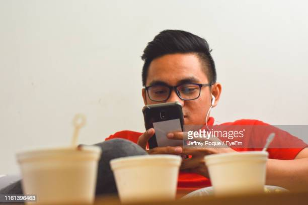 low angle view of man using smart phone - jeffrey roque stock photos and pictures