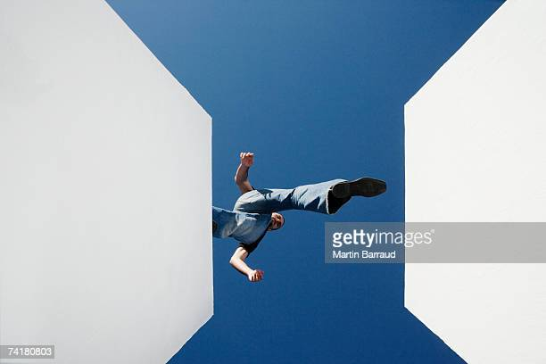 low angle view of man walking across high gap outdoors - high up stock pictures, royalty-free photos & images