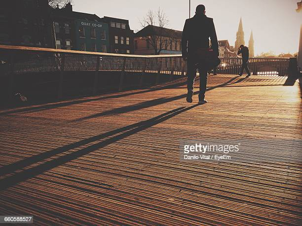 Low Angle View Of Man Walking On Boardwalk During Sunny Day In City
