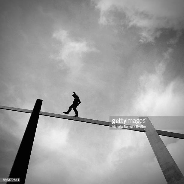 Low Angle View Of Man Walking On Rope