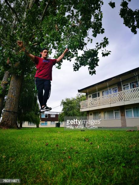 Low Angle View Of Man Walking On Tightrope At Back Yard