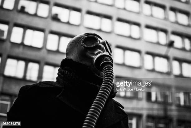 low angle view of man wearing gas mask - gas mask stock pictures, royalty-free photos & images