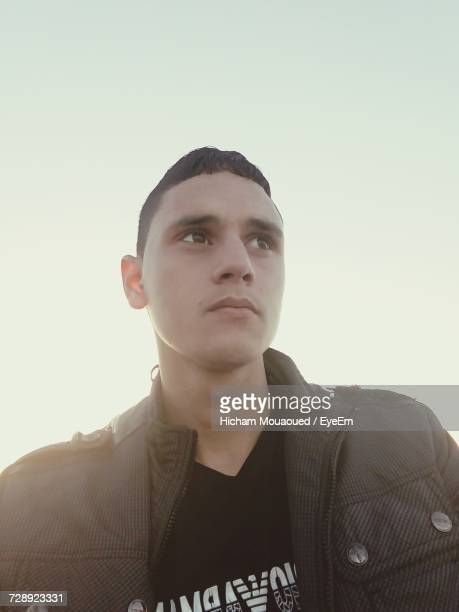 Low Angle View Of Man Wearing Jacket Looking Away Against Clear Sky