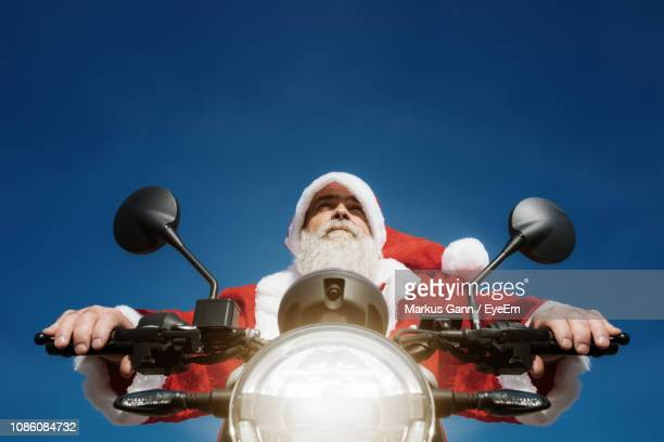 Low Angle View Of Man Wearing Santa Claus Costume Riding Motorcycle Against Clear Blue Sky