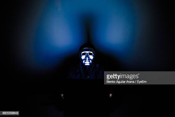 Low Angle View Of Man Wearing Shiny Mask Against Illuminated Black Background