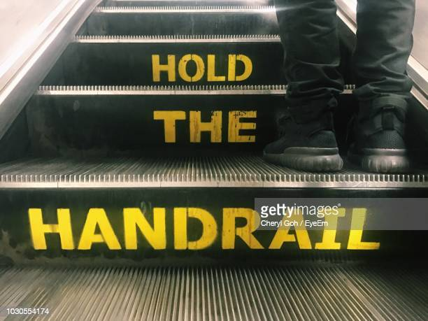 low angle view of man wearing shoes standing on escalator - railings stock pictures, royalty-free photos & images
