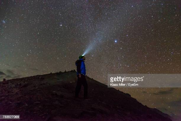 Low Angle View Of Man With Headlamp While Standing On Annapurna Mountain Against Star Field At Night