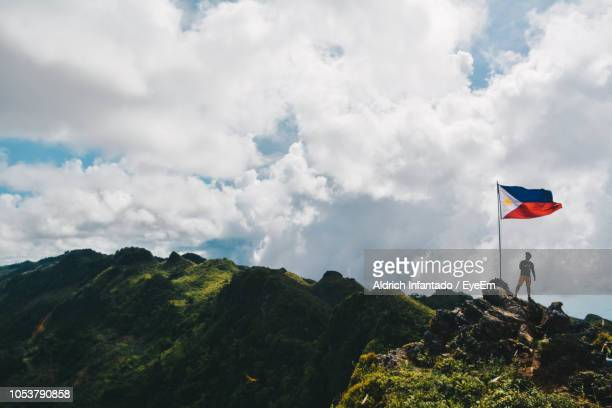 low angle view of man with philippines flag on mountain against cloudy sky - philippines flag stock pictures, royalty-free photos & images