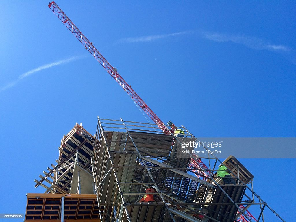 Low Angle View Of Man Working On Construction Site Against Blue Sky : Stock Photo
