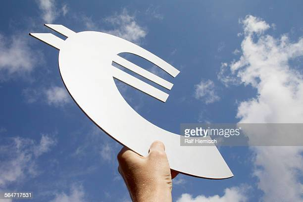 low angle view of mans hand holding euro symbol against sky - environmental signs and symbols stock pictures, royalty-free photos & images