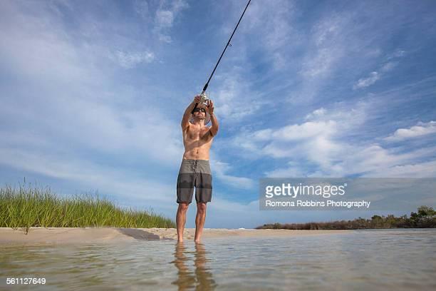 low angle view of mature man fishing, fort walton, florida, usa - golfküstenstaaten stock-fotos und bilder
