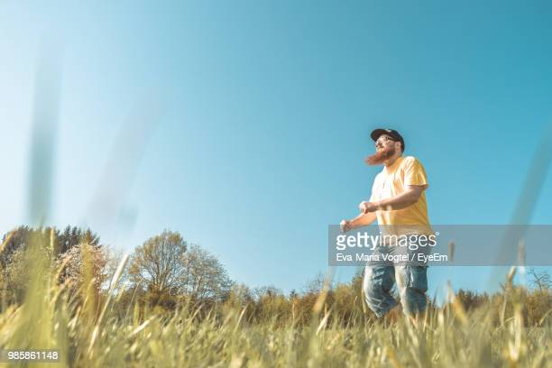 Low Angle View Of Mature Man Jumping On Grassy Field Against Clear Blue Sky