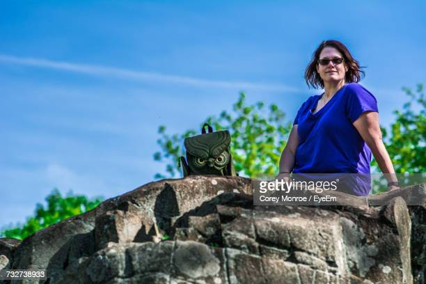 Low Angle View Of Mature Woman Sitting On Rock Against Blue Sky