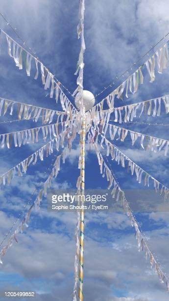 low angle view of may pole with streamers, against clear blue sky - may day stock pictures, royalty-free photos & images