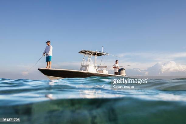 Low angle view of men fishing while standing on boat at sea against sky