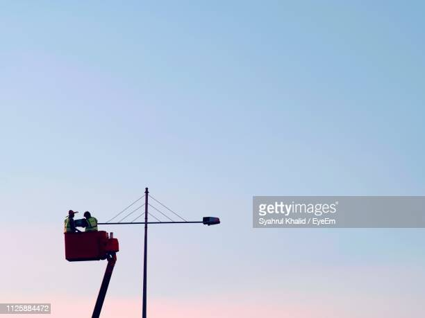 low angle view of men in cherry picker repairing light against clear sky - maintenance engineer stock pictures, royalty-free photos & images