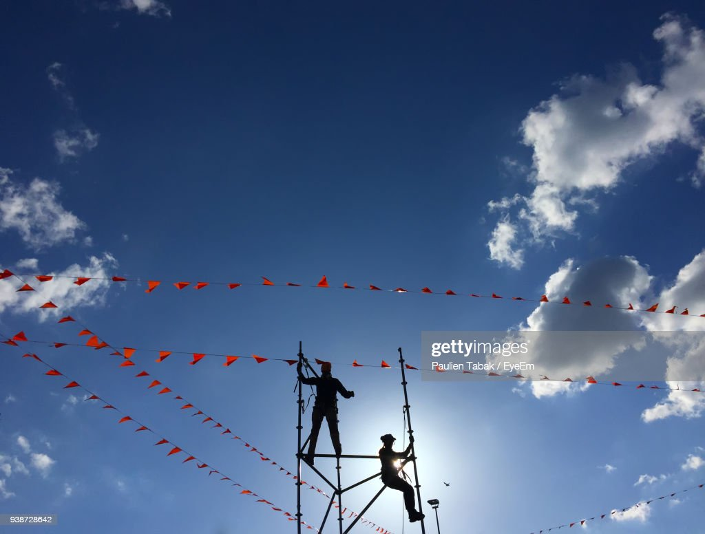 Low Angle View Of Men On Metallic Structure Against Blue Sky : Stockfoto