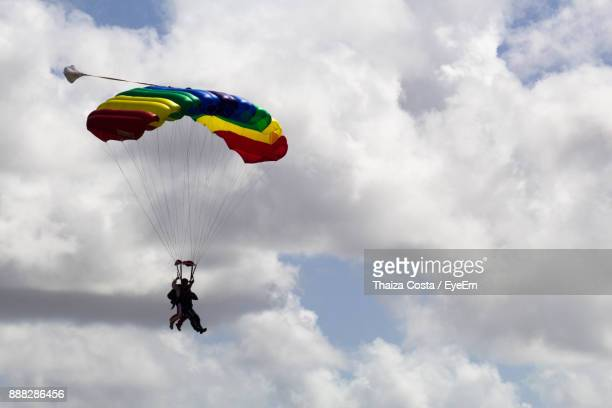 Low Angle View Of Men Paragliding Against Sky
