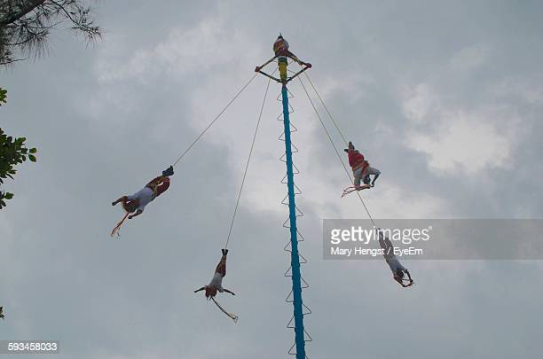Low Angle View Of Men Performing Volador Against Cloudy Sky