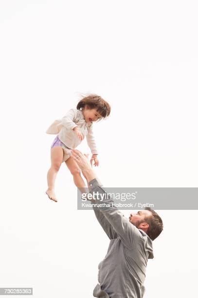 Low Angle View Of Men Playing With Child