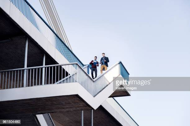Low angle view of men walking on steps by bridge against clear sky