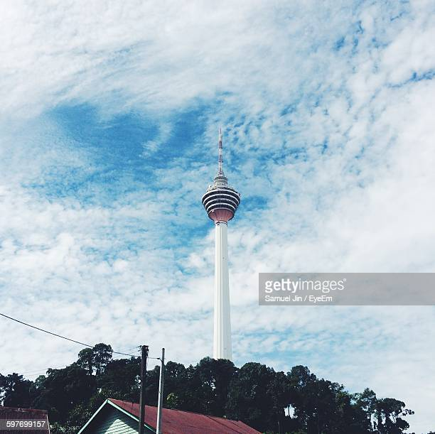 low angle view of menara kuala lumpur tower against cloudy sky - menara kuala lumpur tower stock photos and pictures