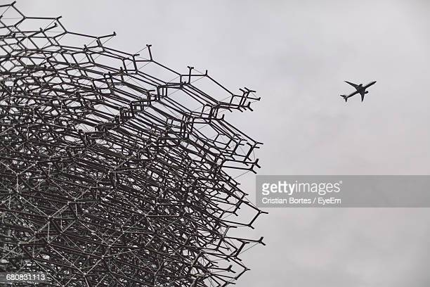 low angle view of metal grate and airplane flying against clear sky - bortes stockfoto's en -beelden
