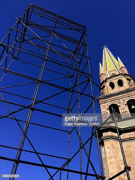 Low Angle View Of Metal Scaffolding With Steeple Against Clear Blue Sky