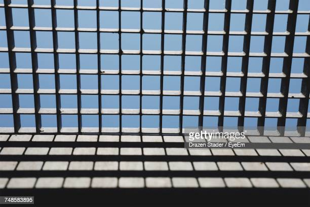 low angle view of metallic grate with shadow on wall against sky - metal grate ストックフォトと画像