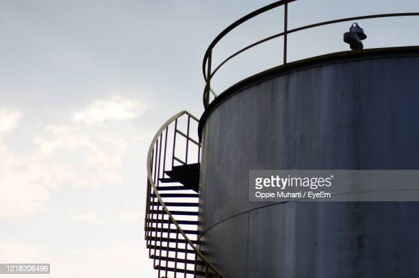 low angle view of metallic structure against sky - water tower storage tank stock pictures, royalty-free photos & images