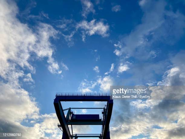 low angle view of metallic structure of crane against blue sky - klaus-dieter thill stock-fotos und bilder