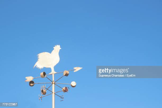 Low Angle View Of Metallic Weather Vane On Blue Sky