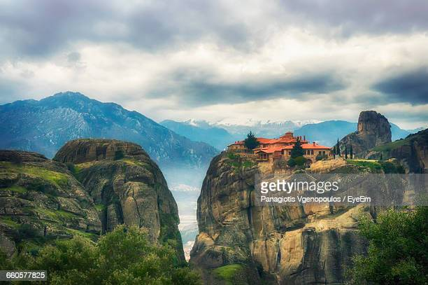 low angle view of meteora against cloudy sky - vgenopoulos stock pictures, royalty-free photos & images