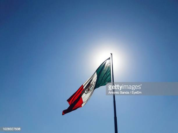 low angle view of mexican flag against clear blue sky - mexican flag stock pictures, royalty-free photos & images