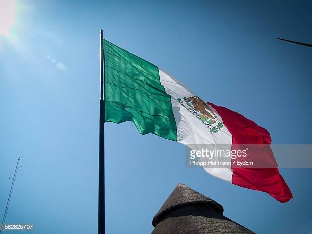 Low Angle View Of Mexican Flag Flying Against Clear Blue Sky