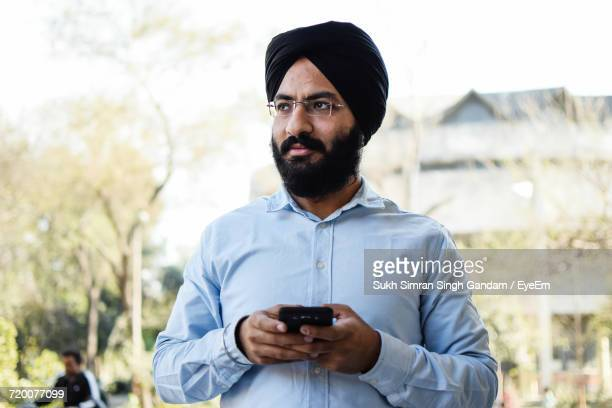 Low Angle View Of Mid Adult Man Wearing Turban While Holding Mobile