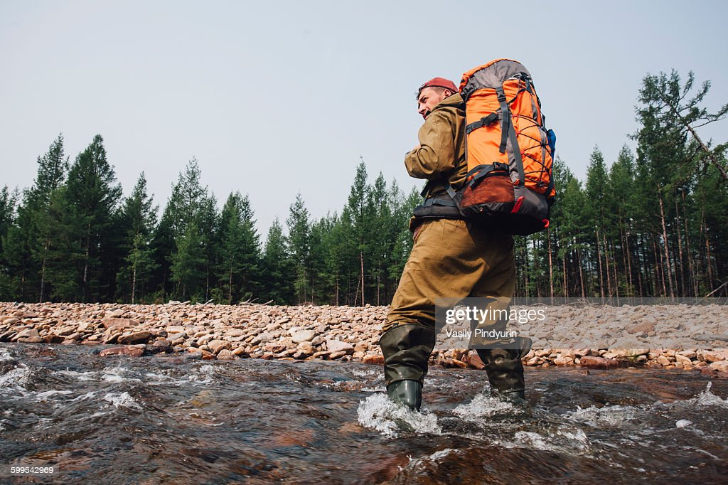 Low angle view of mid adult man with backpack standing in river at forest : Stock Photo