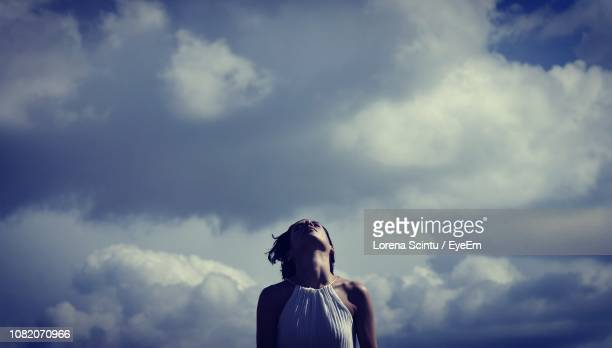 low angle view of mid adult woman standing against cloudy sky - guardare in su foto e immagini stock
