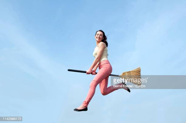 low angle view of mid adult woman with broom levitating against sky during sunny day - witch flying on broom stock photos and pictures