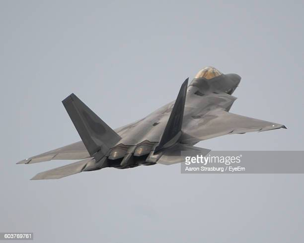 low angle view of military airplane flying against sky - fighter stock pictures, royalty-free photos & images