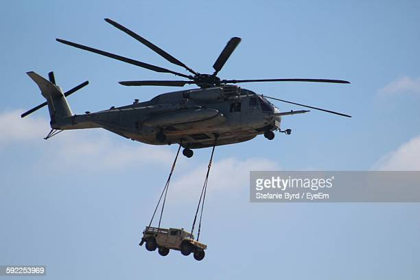 Low Angle View Of Military Helicopter Carrying Jeep Against Sky