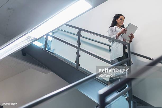 low angle view of mixed race doctor reading medical chart on staircase - down blouse photos et images de collection