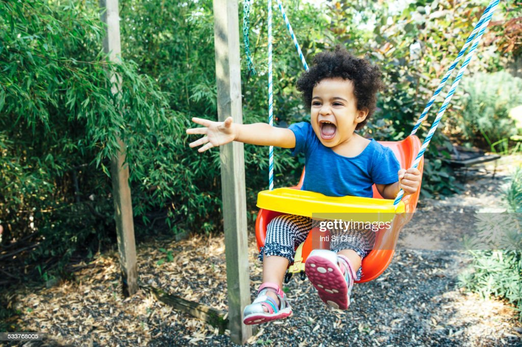 Low angle view of mixed race girl shouting on swing : Foto stock