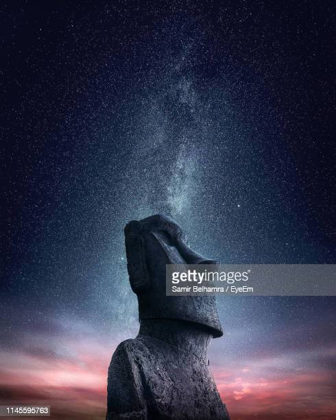 low angle view of moai statue on mountain against starry sky at night - easter island stock pictures, royalty-free photos & images