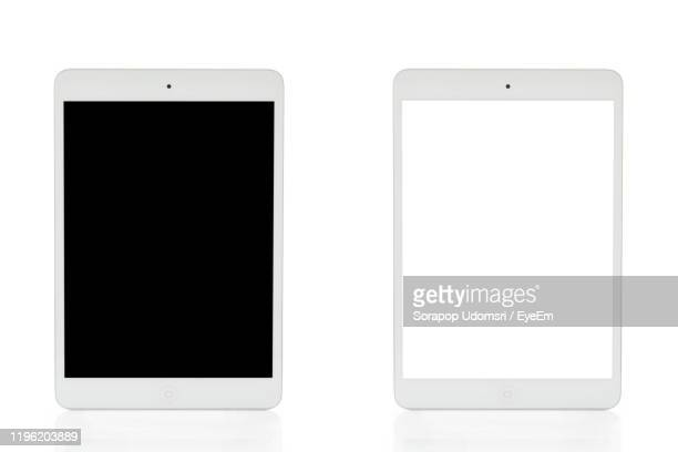 low angle view of mobile phone against white background - tablette photos et images de collection