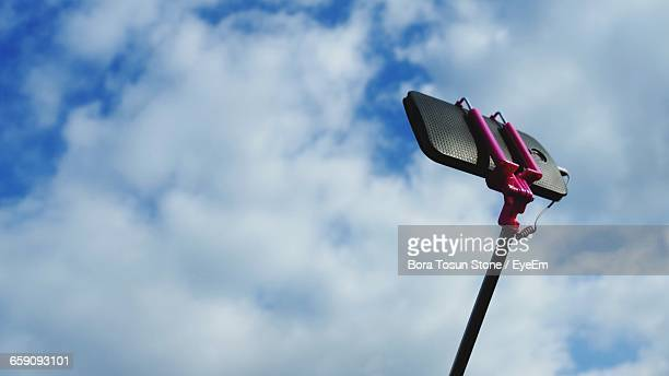 Low Angle View Of Mobile Phone On Monopod Against Cloudy Sky
